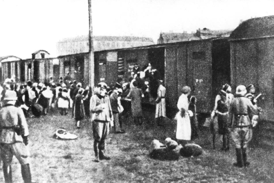 Juden aus dem Warschauer Getto werden im Sommer 1942 in Güterwaggons verladen und in ein Vernichtungslager transportiert.