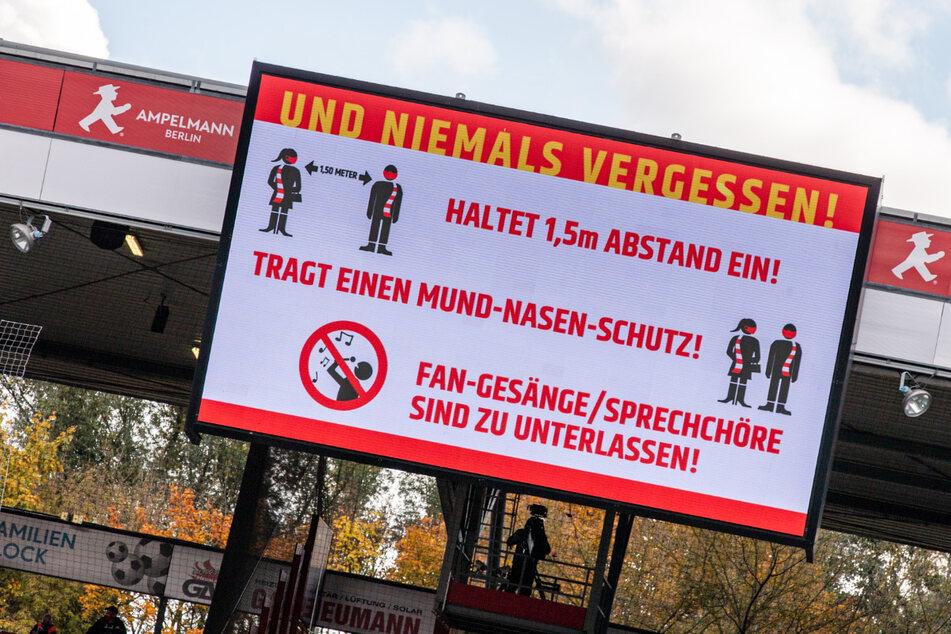 Die Leinwand im Stadion An der Alten Försterei in Berlin zeigt den Schriftzug: Und niemals vergessen! Haltet 1,5m Abstand ein! Tragt einen Mund-Nasen-Schutz! Fan-Gesänge / Sprechchöre sind zu unterlassen!