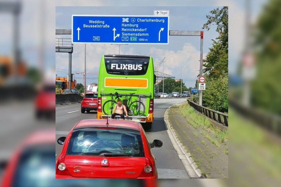 Ein unbekannter Mann sitzt in aller Ruhe auf der Halterung für Fahrräder am Heck eines Flixbusses, der über die Berliner Stadtautobahn fährt.