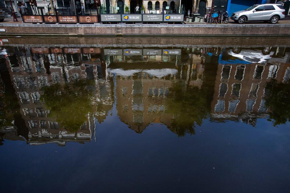 """Der Coffeeshop """"The Bulldog"""" in AMsterdam spiegelt sich im Kanal Oudezijds Voorburgwal. Nach Einführung der strengen Corona-Maßnahmen ist der Konsum von illegalen Drogen in Amsterdam stark zurückgegangen."""
