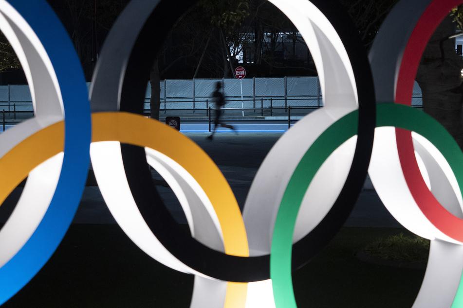 Ein Jogger ist durch einen Olympischen Ring zu sehen. Japans Olympiamacher können die Kosten für die Verlegung der Olympischen Sommerspiele ins nächste Jahr noch immer nicht beziffern.