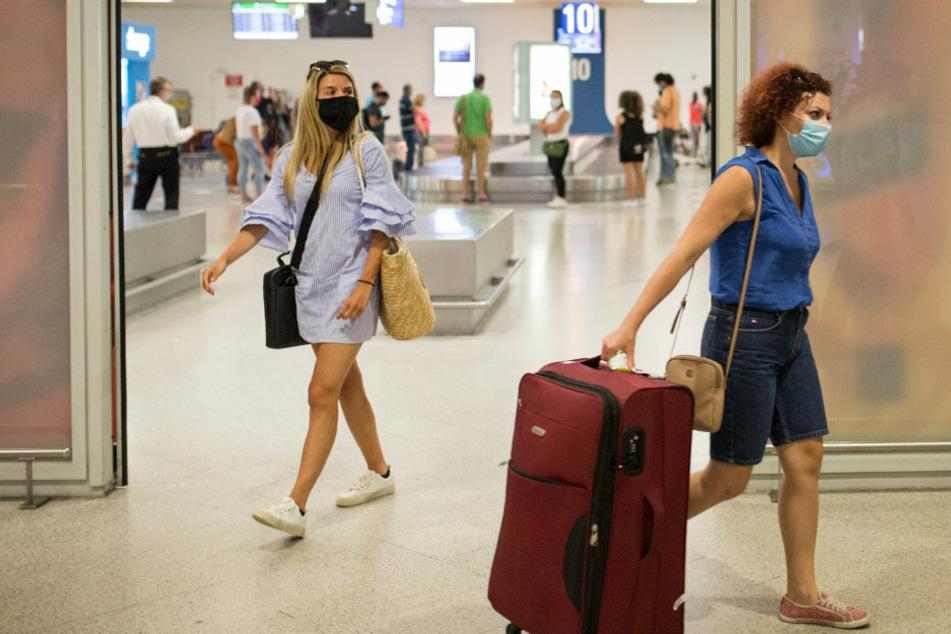 Reisende mit Mundschutz kommen auf dem Athener Flughafen an.