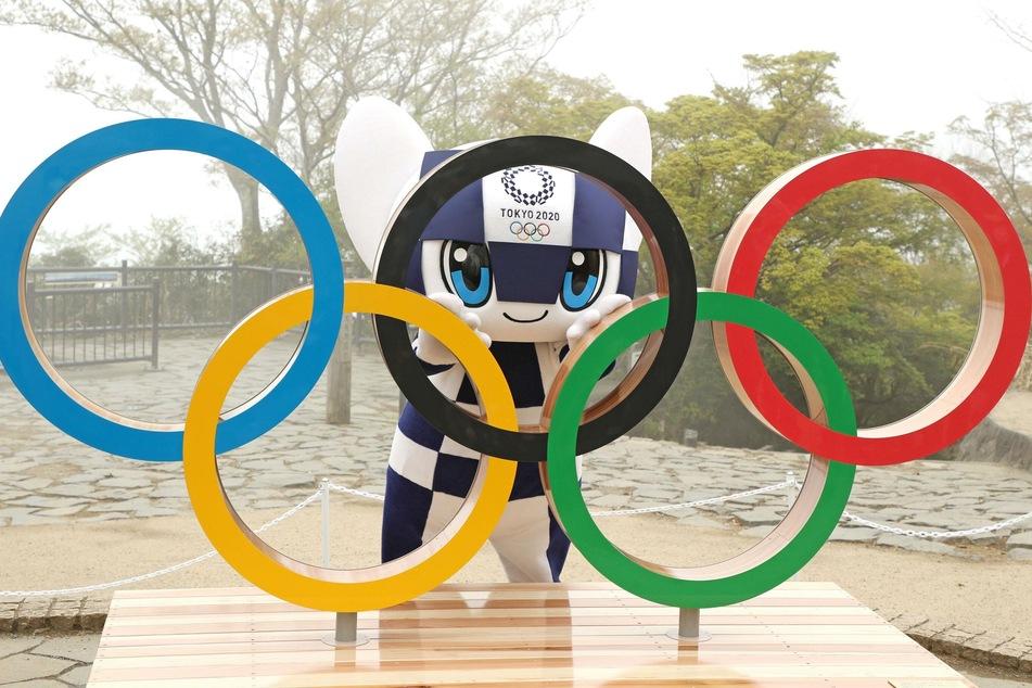 Das Maskottchen Miraitowa steht vor dem Beginn der Olympischen Spiele hinter den Olympischen Ringen in Hachioji.