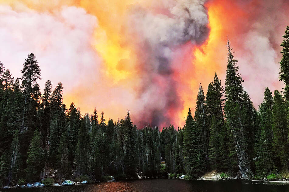 Smoke rises from a forest fire behind Huntington Lake.