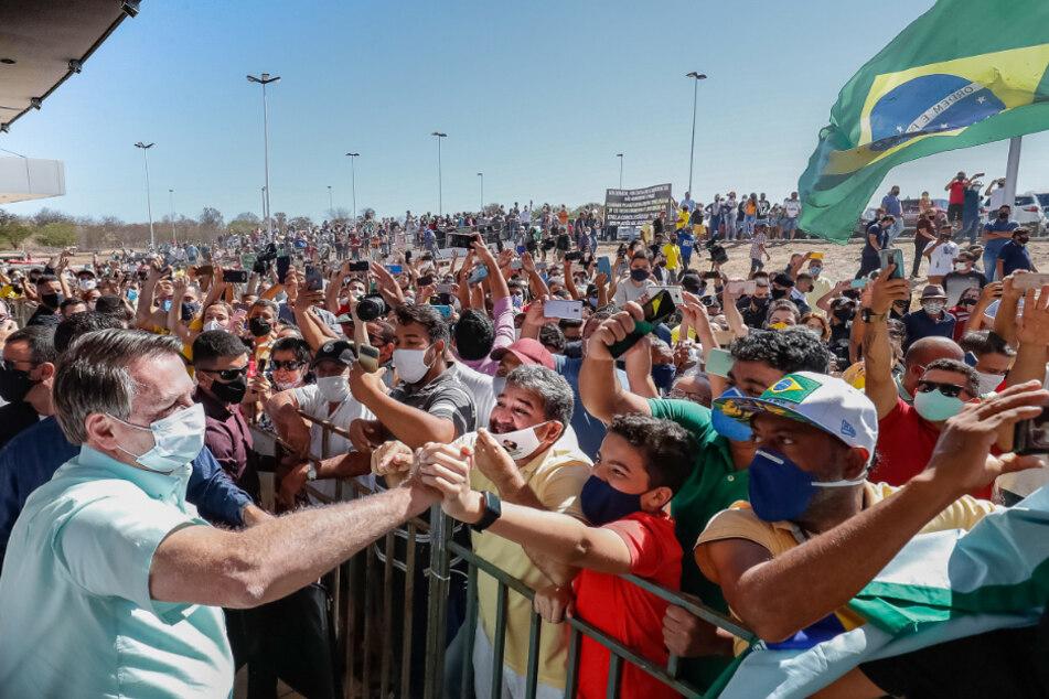 Sao Raimundo Nonato: Auf diesem vom brasilianischen Präsidentenamt zur Verfügung gestellten Bild schüttelt der vor wenigen Tagen wieder negativ auf Covid-19 getestete Präsident Jair Bolsonaro (l) Anhängern die Hand, als er auf dem Internationalen Flughafen Serra da Capivara ankommt.