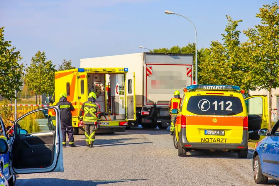 Mehrere Einsatzfahrzeuge von Polizei und Feuerwehr sind am Unfallort eingetroffen. Im Hintergrund ist der am Unfall beteiligte Lkw zu sehen.
