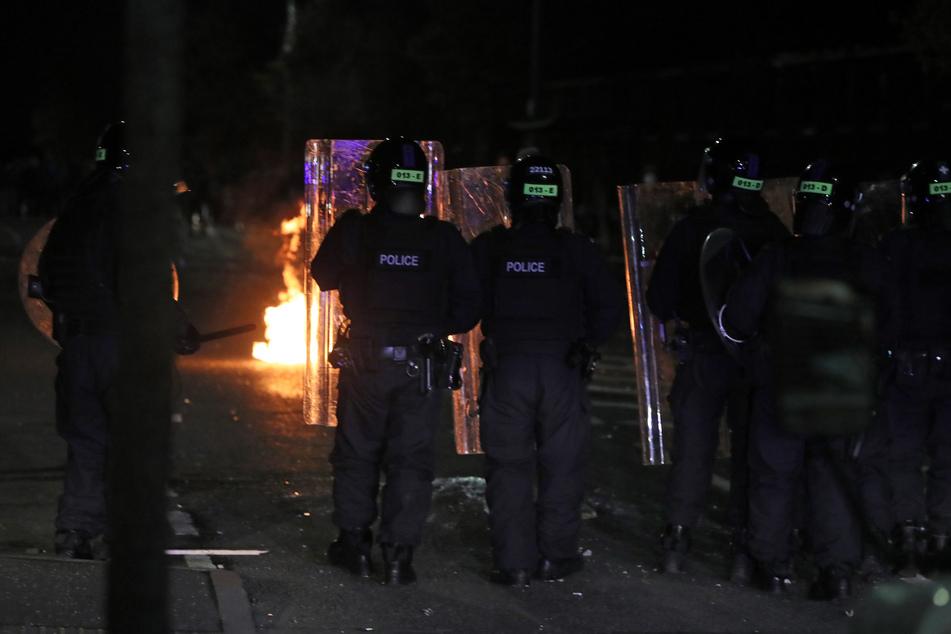Polizisten mit Schutzschilden stehen in einer Straße in der Tigers Bay in Belfast während weiterer Unruhen, bei denen inzwischen Dutzende Beamte verletzt wurden.