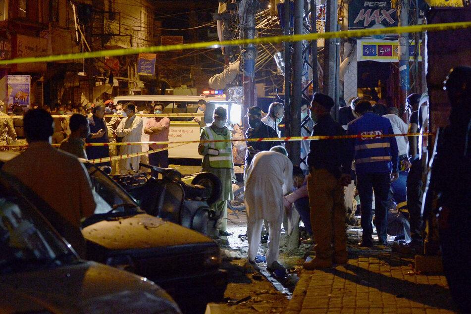 Pakistans Sicherheitsbeamte untersuchen den Ort einer Bombenexplosion, die den Basar in Rawalpindi zerstörte.