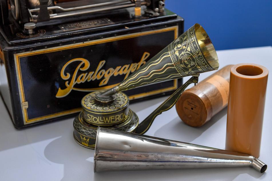 Ein Parlograph von 1910 und ein Phonograph des Schokoladenherstellers Stollwerck neben einer Wachswalze zur Schallaufzeichnung und -wiedergabe.