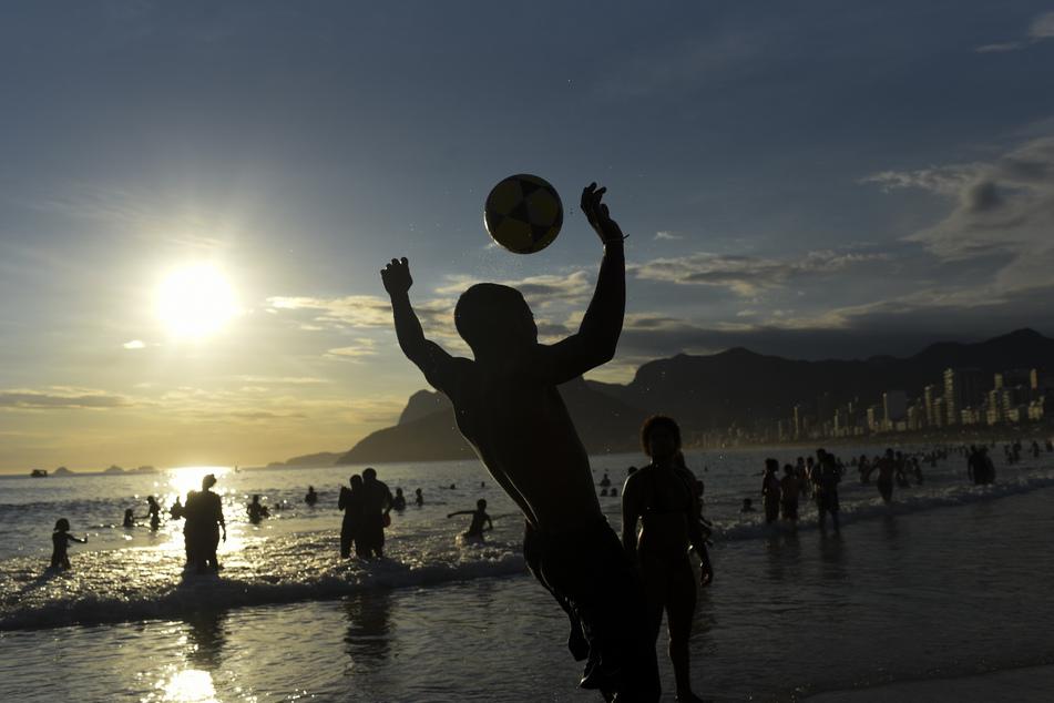 Rio de Janeiro: Jugendliche spielen mit einem Ball bei Sonnenuntergang am Strand von Ipanema.