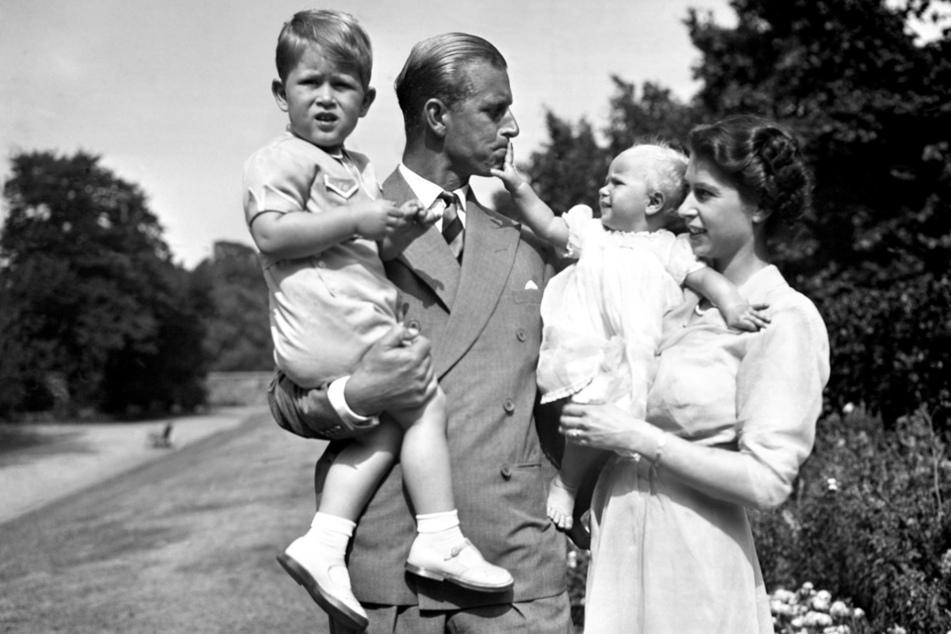 9. August 1951: Prinzessin Elizabeth (re.), die Prinzessin Anne in den Armen hält, und Prinz Philip, Herzog von Edinburgh, der Prinz Charles trägt, stehen auf dem Gelände von Clarence House.