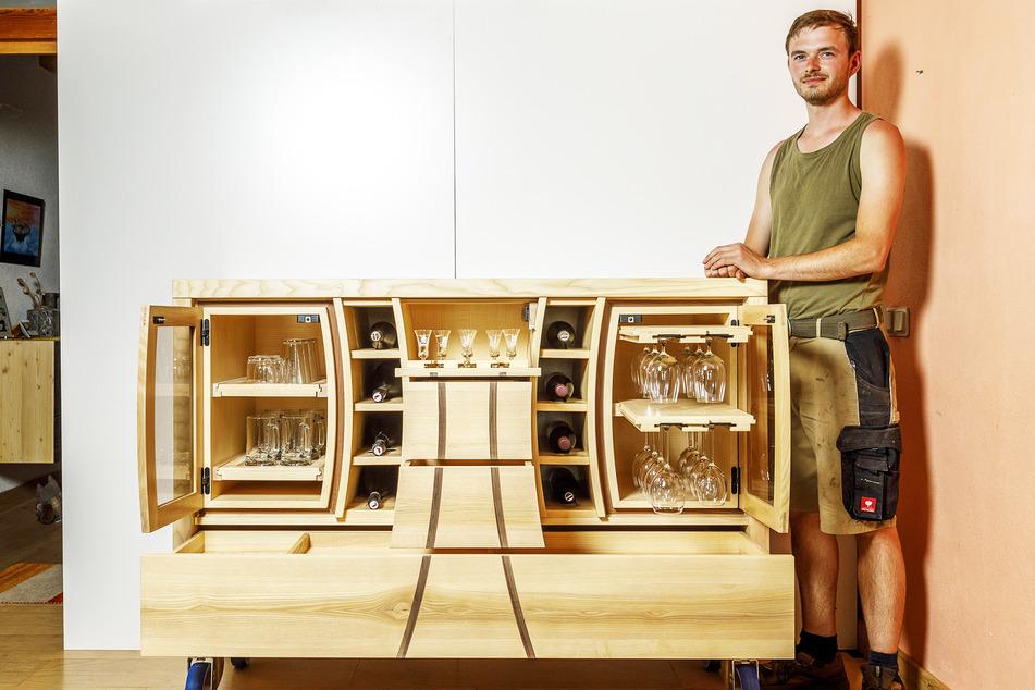 Tischlermeister Benjamin Stamer (28) mit seinem Meisterstück: Die Türen der Hausbar lassen sich nur mittels Handy-App öffnen.