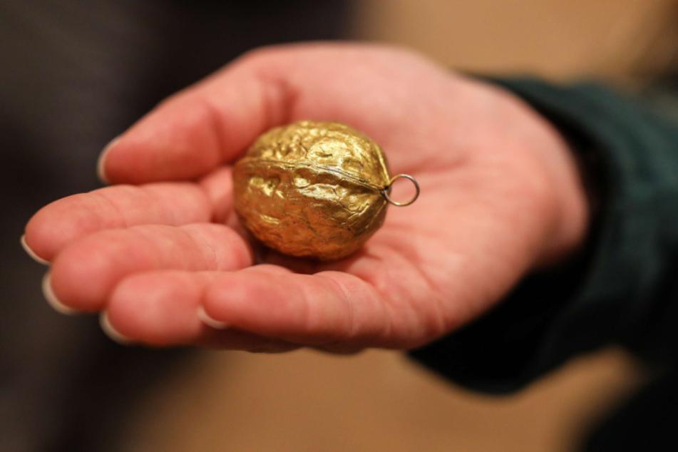 In einer geöffneten Hand liegt eine goldene Walnuss.