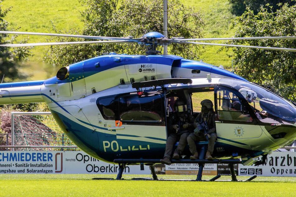 Polizisten eines SEK sitzen in der Tür eines gerade gelandeten Hubschraubers.