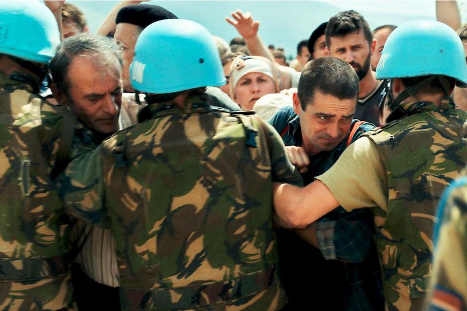Hamdija Selmanagic (Boris Ler, 36, 2.v.r.) und sein Vater Nihad (Izudin Bajrovic, 58) versuchen, auf den UN-Stützpunkt vorzudringen, was von den Blauhelmen verhindert wird.