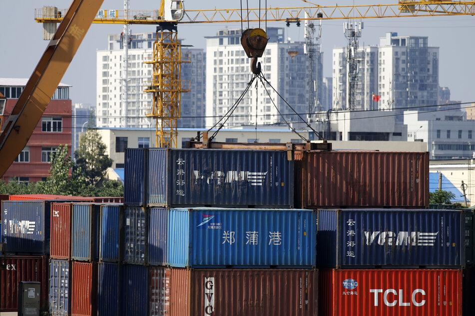 Vor Containern wird auf einer Baustelle in der Nähe des Dayun-Flusses in Huaian in der ostchinesischen Provinz Jiangsu eine Stahlkonstruktion errichtet.