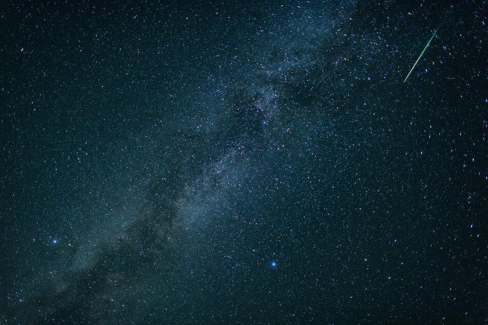 Bayern, Einsiedl: Eine Sternschnuppe leuchtet neben der Milchstraße am Himmel über dem Walchensee. Jedes Jahr im August sind im Sternschnuppenstrom der Perseiden zahlreiche Sternschnuppen zu sehen. (Archivbild)