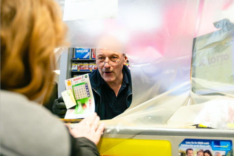 Ein Supermarkt-Mitarbeiter spricht mit einer Kundin durch eine Plastikfolie hindurch.