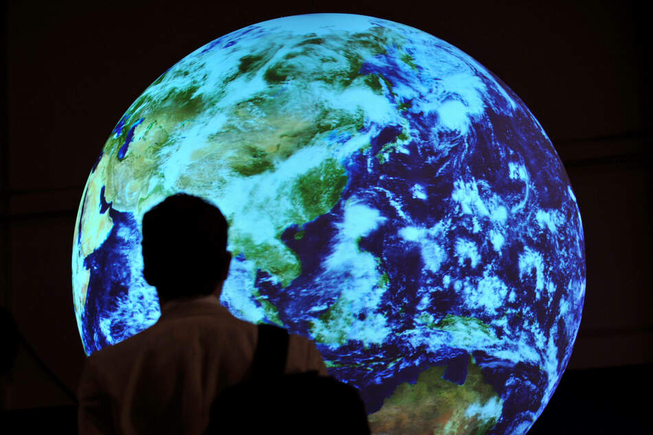 A man walks past an Earth model at the conference hall of the 2009 United Nations Climate Change Conference in Copenhagen.
