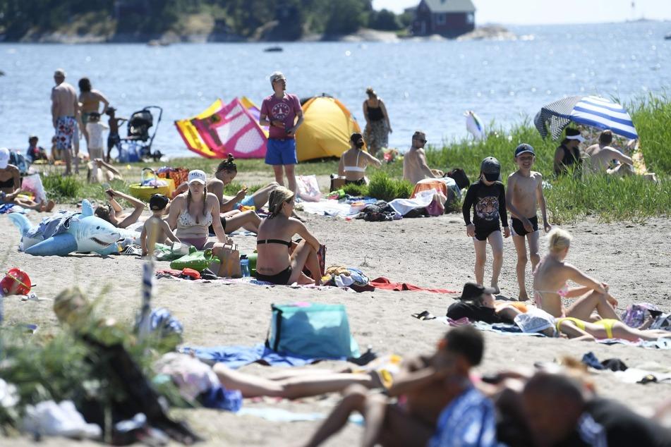 Menschen genießen den heißen, sonnigen Tag an einem Strand in Helsinki.