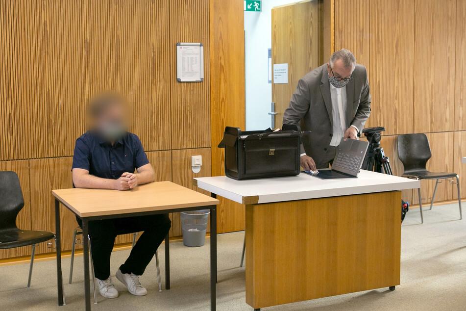 Der Angeklagte sitzt im Sitzungssaal vom Landgericht neben seinem Anwalt.