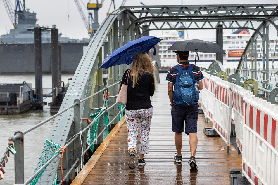 Mit Regenschirmen schützen sich eine Frau und ein Mann bei einem Spaziergang im Hamburger Hafen.
