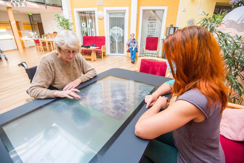 Heimbewohnerin Sabine Schulz (68) probiert zusammen mit Pflegerin Claudia Becher ein Spiel am neuen Computertisch aus