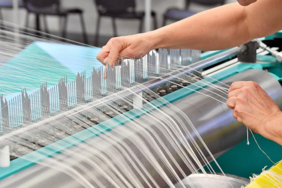 """Thüringen, Gera: Eine Mitarbeiterin bestückt in einer Textilweberei die sogenannte """"Zettelmaschine"""" mit Garn."""
