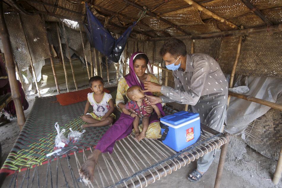 Ein Mitarbeiter des Gesundheitswesens mit medizinischem Mundschutz impft ein kleines Kind in der pakistanischen Stadt Lahore.