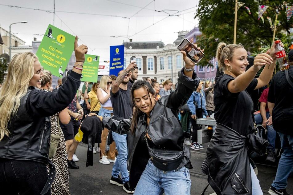 """Teilnehmer eines Protestmarsches unter dem Motto """"Unmute Us"""" (etwa: """"Schaltet unsere Mikros wieder an"""") zogen am 11. September durch Den Haag. Nun machen die Niederlande einen vorsichtigen Schritt zur Normalität: Kein Sicherheitsabstand mehr in Gaststätten und Geschäften."""