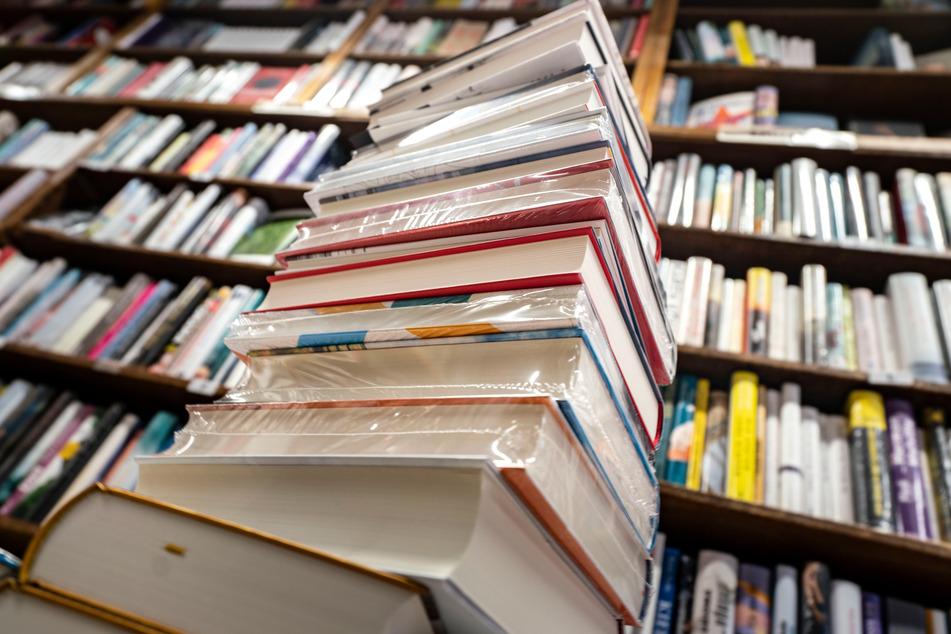 Ein Stapel neuer Bücher liegt auf einem Verkaufstisch in einer Buchhandlung.