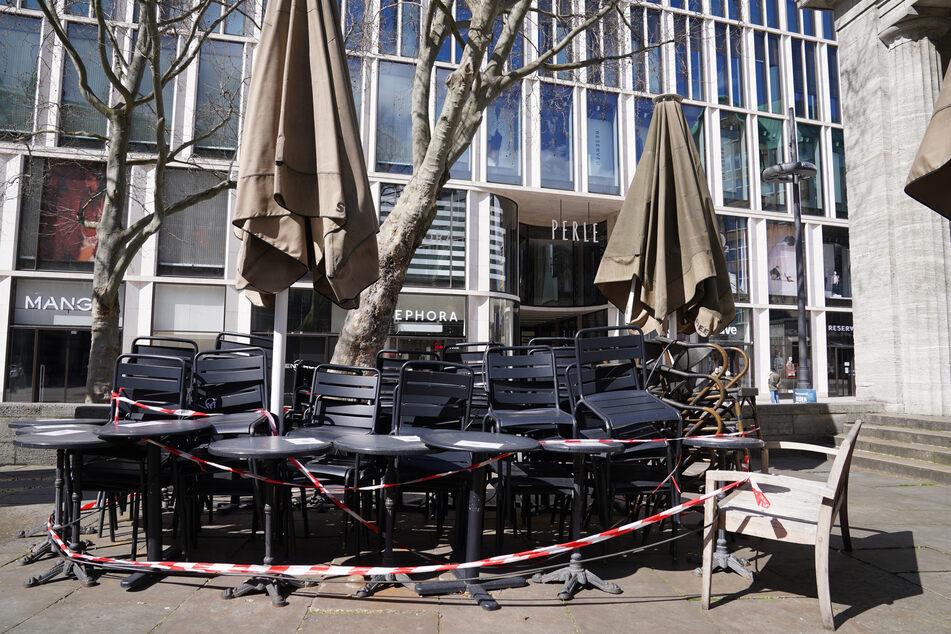 Tische und Stühle stehen abgesperrt mit Flatterband im Außenbereich eines Gastronomiebetriebes in der Innenstadt. Der Corona-Lockdown in Hamburg wird verlängert.