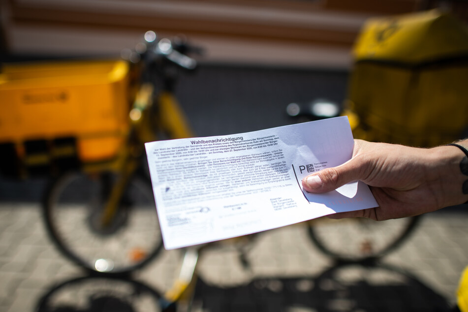 Ein Briefträger der Deutschen Post hält eine Wahlbenachrichtigung in der Hand. Stimmzettel können bis spätestens zwei Tage vor der Wahl bestellt werden. (Symbolbild)