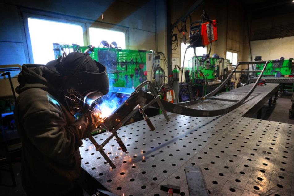 """Ein Mitarbeiter des Pumptrack-Herstellers """"Schneestern"""" schweißt in der Produktionshalle der Firma an einem Metallgerüst."""