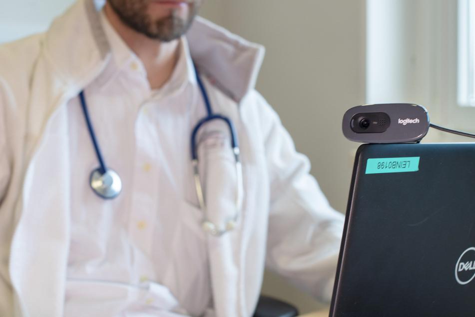 Ein Hausarzt spricht während einer Videosprechstunde in seiner Praxis mit einer Patientin. (Archivbild)