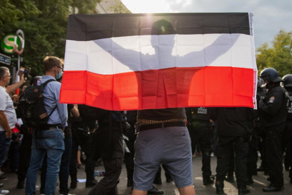 Ein Mann hält eine Reichsflagge bei einem Protest gegen die Corona-Maßnahmen vor der russischen Botschaft. (Symbolbild)