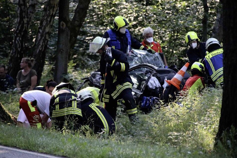 Rettungshelfer arbeiten zusammen am Wrack eines PKW der mit drei Insassen über die Böschung an einen Baum geprallt ist.