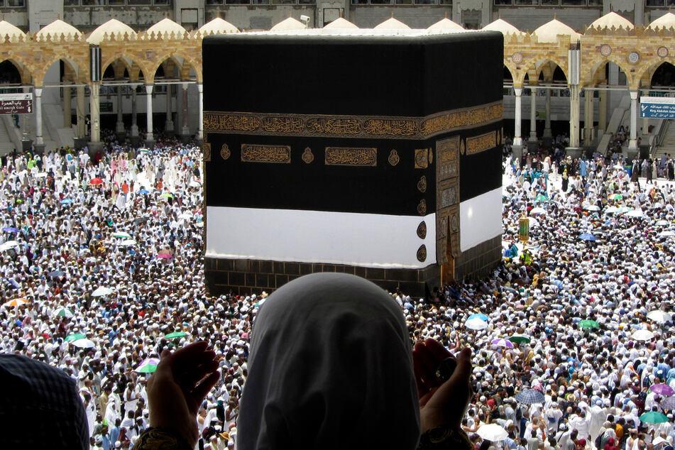 Mekka: Eine muslimische Pilgerin betet, während sie zuschaut, wie Tausende von Pilgern bei der Hadsch-Pilgerfahrt um die Kaaba herumgehen. (Archivbild)