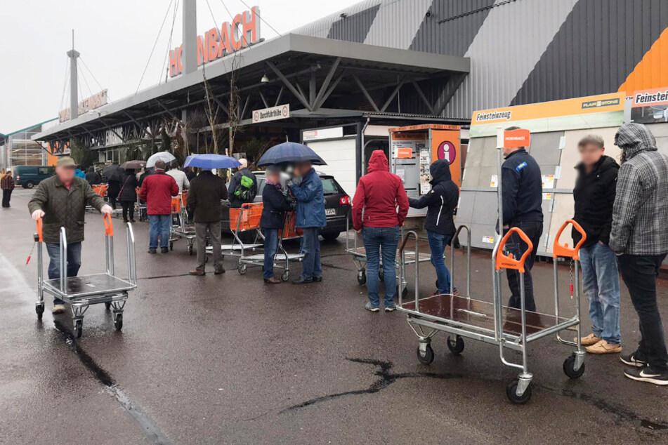 Dutzende Menschen warten vor dem Hornbach in Übigau.