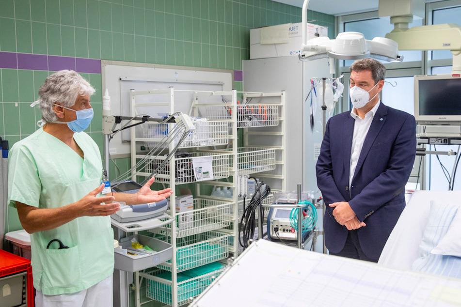 Markus Söder (r, CSU), bayerischer Ministerpräsident, unterhält sich bei einem Besuch im Klinikum Nürnberg Süd mit Stefan John, Oberarzt und Abteilungsleiter der internistischen Intensivstation der Klinik für innere Medizin mit Schwerpunkt Kardiologie, in einem Aufnahmeraum vor der Intensivtation.