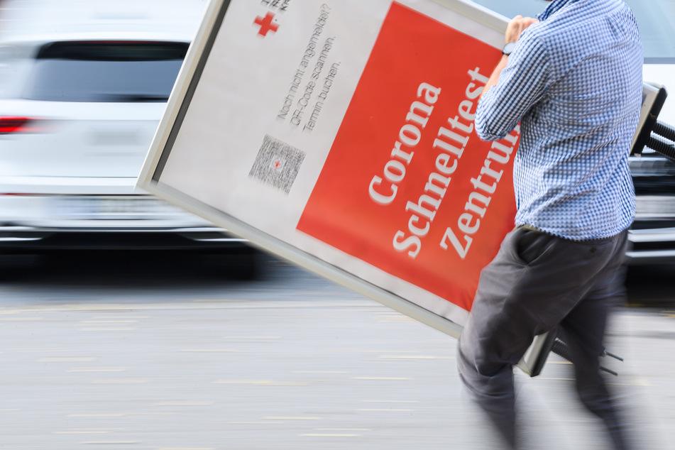 Ein Mitarbeiter des DRK Dresden trägt ein Hinweisschild für ein Corona Schnelltest Zentrum nach dem Abbau der Teststelle weg.