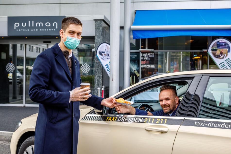 Azubi Florian May (18) bringt Taxifahrer Alexander Noack (44) einen Geburstagskaffee ans Auto.
