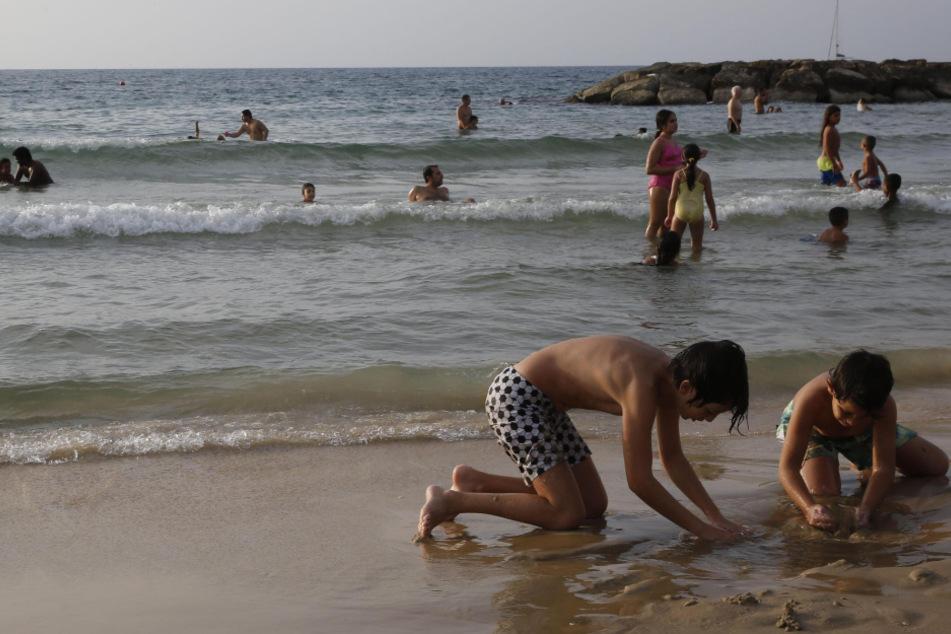 Israel, Aschkelon: Zwei Kinder buddeln am Strand. Der einmonatige landesweite Lockdown zur Eindämmung der Corona-Pandemie wurde aufgehoben.