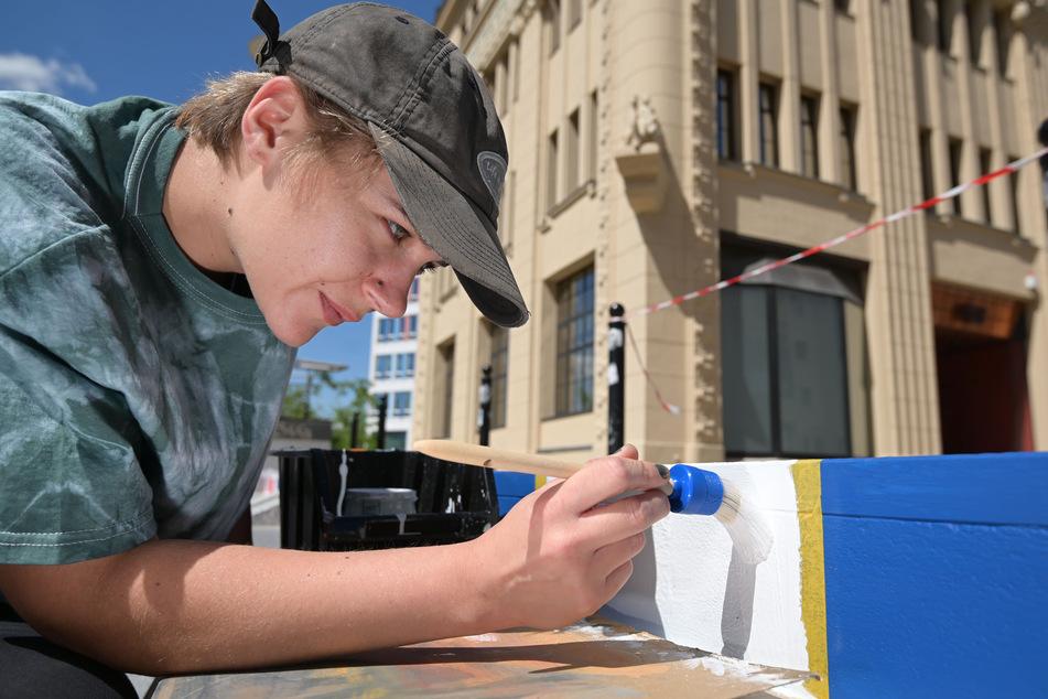 Emily König (23) trägt mit einem Pinsel strahlendes Weiß auf eine der 20 Stufen auf.