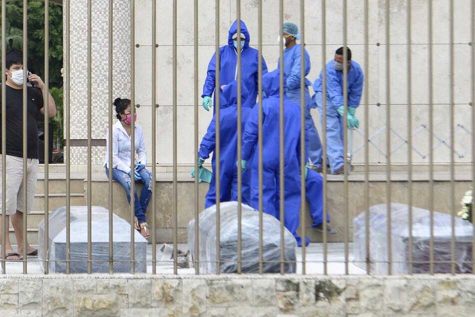 Verwandte und das Friedhofspersonal warten darauf, die Särge mutmaßlicher Opfer des neuartigen Coronavirus zu beerdigen.