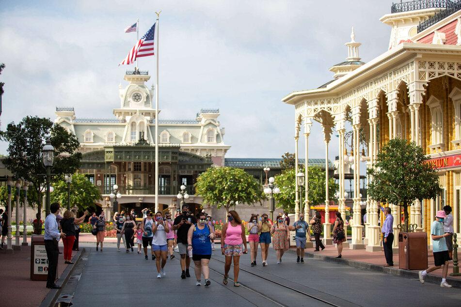 """Gäste des Freizeitparks """"Walt Disney World"""" gehen durch den Park am Tag der Wiedereröffnung."""