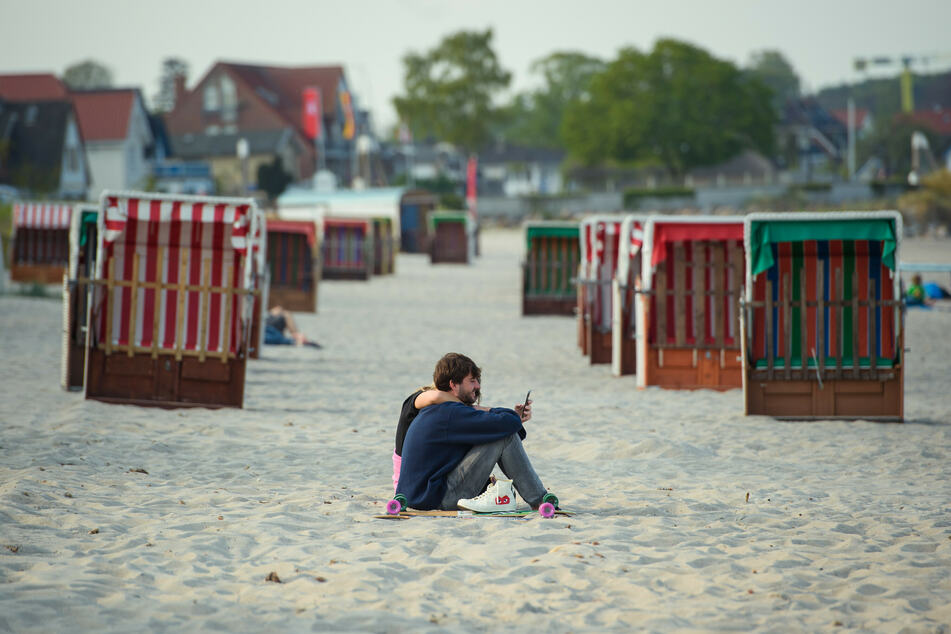 Ein Paar sitzt vor zwei Reihen geschlossener Strandkörbe am Strand in Scharbeutz.