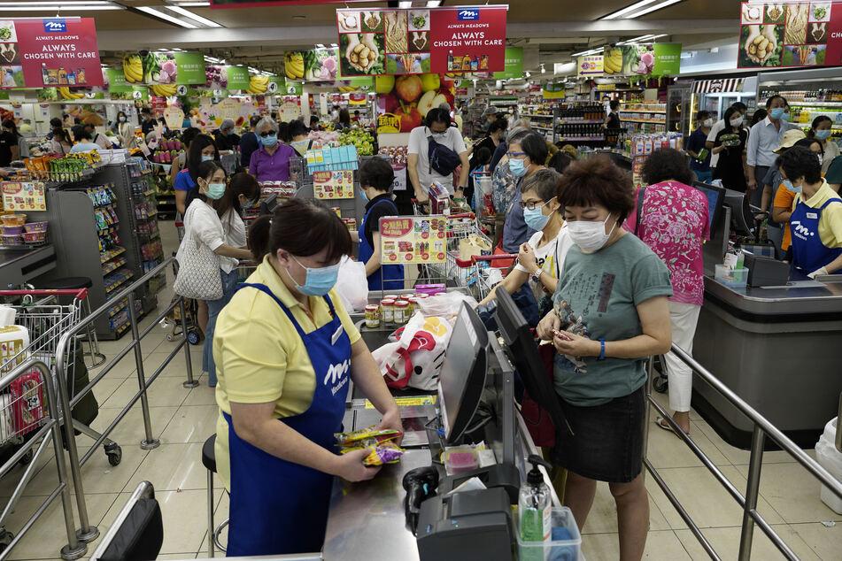 Zahlreiche Kunden tragen in einem Supermarkt in Hongkong einen Mundschutz.
