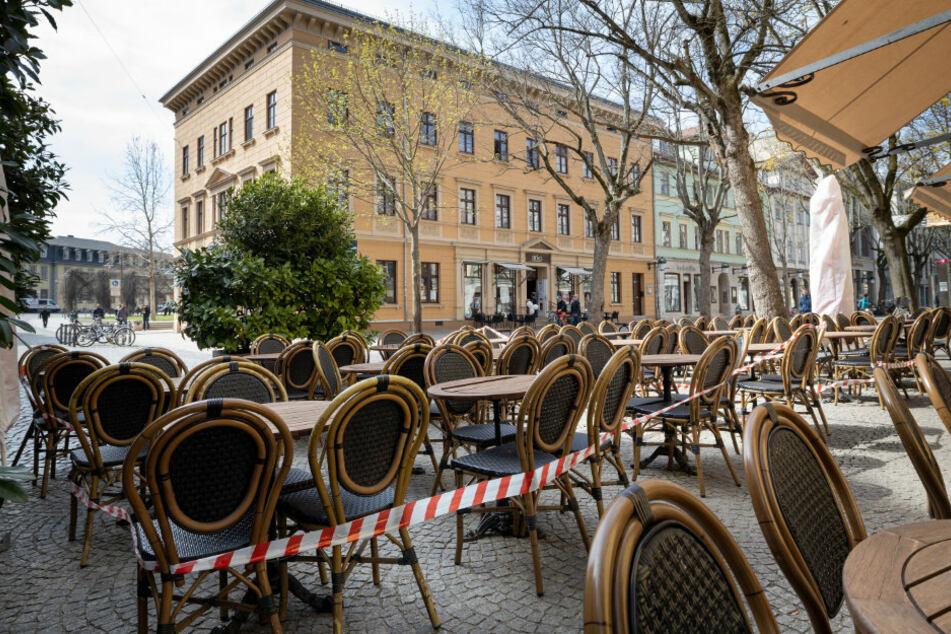 Absperrband ist um die Tische und Stühle vor einem Restaurant in der Innenstadt gezogen.