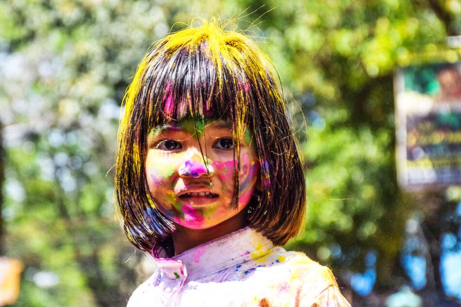 Ein mit Farben besprühtes Mädchen nimmt an den Feierlichkeiten zum Holi-Festival in Kalkutta, Indien teil.